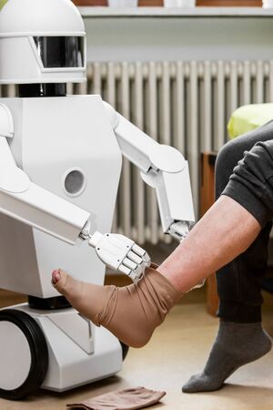 caregiver robot or medical assisted living robot is putting on a compression stocking on an senior adults leg