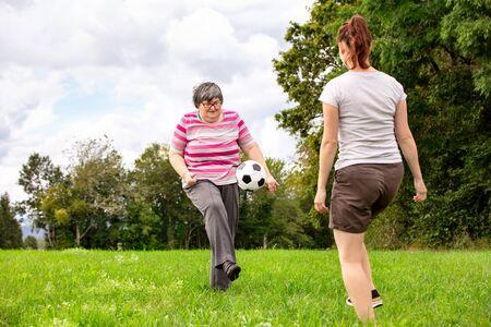une femme handicapée mentale joue au football pour entraîner ses capacités motrices, des exercices avec un ami ou un thérapeute à l'extérieur sur un pré Banque d'images