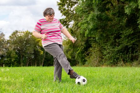mental disabled woman is playing soccer to train her motor abilities, funny exercises outdoors on a meadow