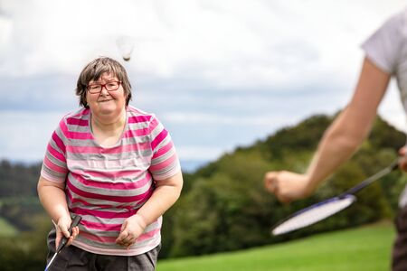 mental disabled woman is playing badminton to train her motor abilities, exercises with a friend or therapist outdoors on a meadow
