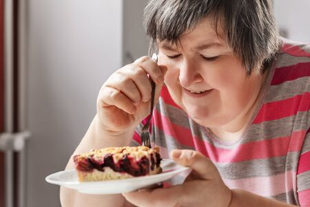 mental disabled woman is eating a plum pie while sitting in the kitchen