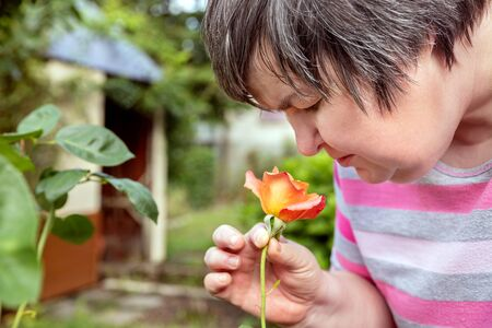 mental disabled woman is smelling on a rose outdoor in the garden Stockfoto