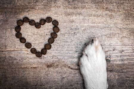 Dog´s Paw and heart shaped goodies or kibbles on wooden Table, concept Love of Animals