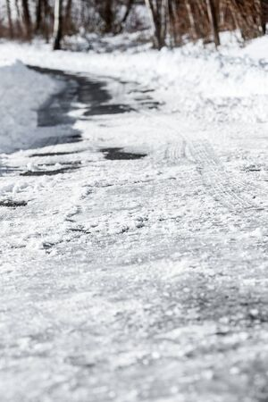Black ice and snow on the country road or street, danger and accident risk at the winter season, copyspace