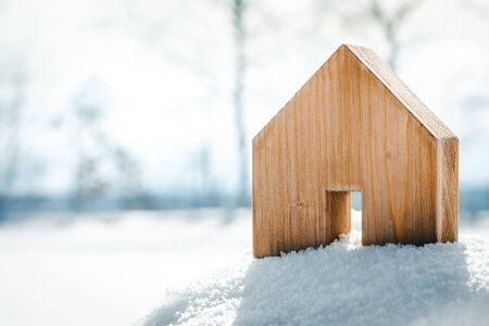 Small wooden House standing in the snow, planning Housebuilding on the building area, copyspace