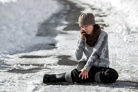 Woman slipped on winter road with black ice, emergency call for help, accident and injury, copyspace