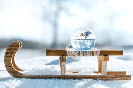 Wooden sledge with a crystal or glass ball, winter landscape reflection with christmas balls, copyspace Stock fotó
