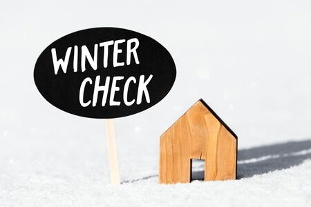 Little wooden House and Sign in the Snow, Text Winter Check, Concept inspection and service for the own home