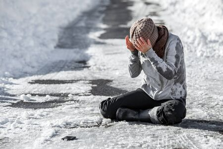 Woman slipped on the winter road, accident and injury, black ice and danger, copyspace