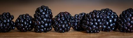Panorama, closeup of fresh raw blackberries on wooden table, Rubus sectio rubus