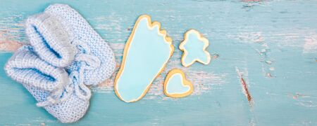 Header for Birth from a newborn boy, blue cookies and little shoes on blue table, copyspace