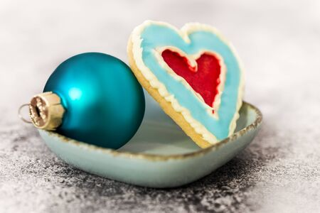 leckerer Herzformkeks und blauer Weihnachtsball auf einem grauen Tisch Standard-Bild