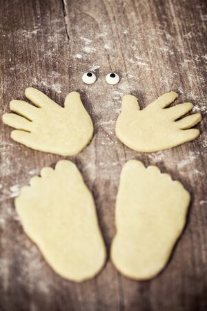white Cookies shaping a figure with hands, feets and eyes on wooden table