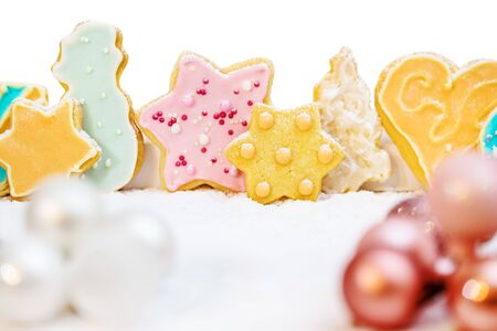 christmas cookies with colorful frosting, baubles and icing sugar in front of white, greeting card