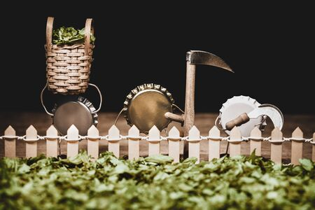 Crown cork miniature figures standing on a hop yard, harvester with baskets and scythe, humorous conceptual scene for harvesting ingredients for brewing beer Standard-Bild