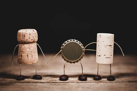 Three different bottle tops, cork for champagne, wine and crown are the best friends, humorous conceptual scene for diversity and variety, friendship and togetherness