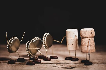 Crown cork, wine and champagne cork miniature figures with a handshake, hilarious conceptual scene for friendship and altruism