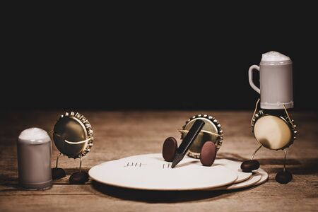 Crown cork miniature figures with a beermat and beer jugs, humorous conceptual scene for tavern or pub bills and gastronomy Stockfoto
