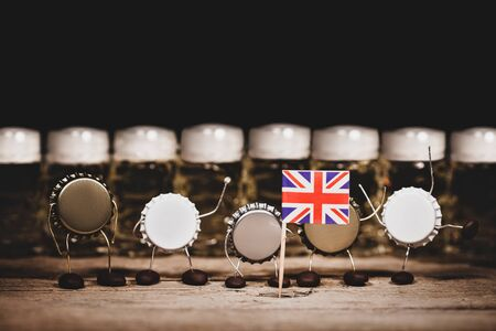 Crown cork miniature figures and beer glasses in the back, great britain flag, humorous conceptual scene for advertising country of origin and beer culture, copyspace