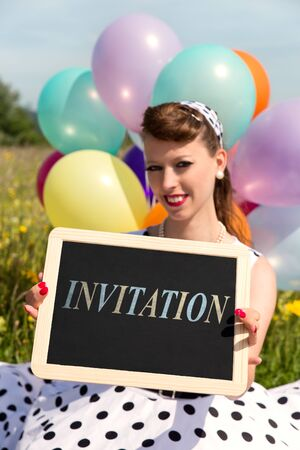 Rockabilly Girl in the nature holding a board with word invitation, concept party 版權商用圖片