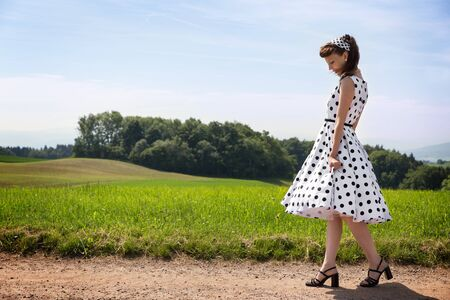 Rockabilly Girl with a white petticoat dress taking a walk to the nature