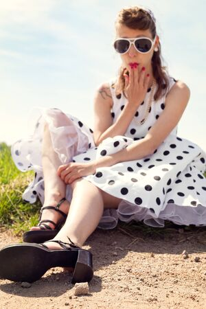 Portrait of a young pretty woman with a vintage rock & roll dress sitting on the wayside