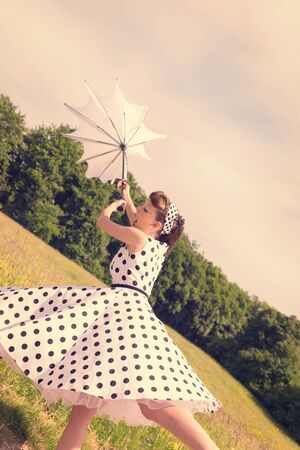 Pin up Girl with a dotted petticoat dress from the fifties and a broken umbrella, filtered