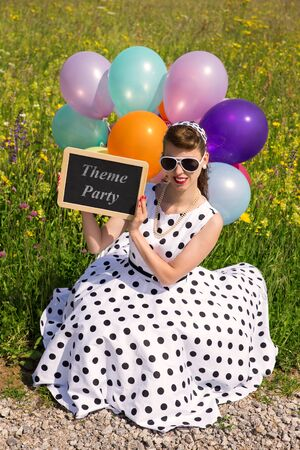 Woman with a rock n Roll dress and colorful balloons holding a slate with text theme party, concept invitation