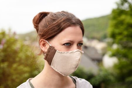 Woman is wearing a homemade fabric cloth face mask, coronavirus, corona and covid-19 prevention and protection