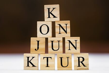 Wooden blocks with german word konjunktur with means conjuncture, stumulus package and finance