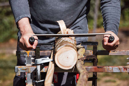 a man is shaving an wooden log with an drawknife Stock Photo