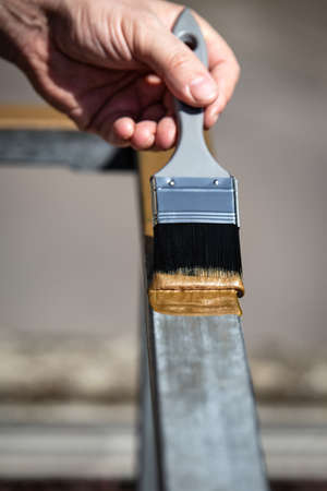 a man is painting a metal railing with copper varnish, close up outdoor shot Standard-Bild