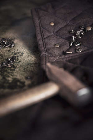 a lot of tools like a hammer and some copper rivets, crafting leathercraft equipment on a brown backgound