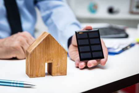 Businessman with a house and a solar panel in the office, concept green energy and economy Stockfoto