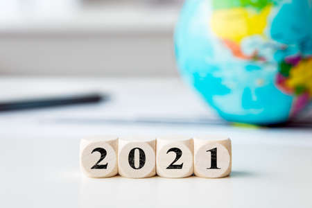 Globe in the background, dice with numbers 2021, new hope and start in the new year without the coronavirus