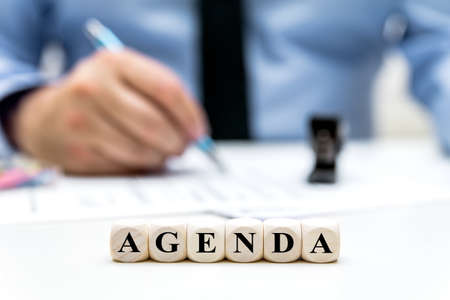 Businessman in the office, dices with word Agenda, planning and order program and strategy