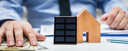 Header, man with us dollars and a house with a solar panel, energy and money Stockfoto