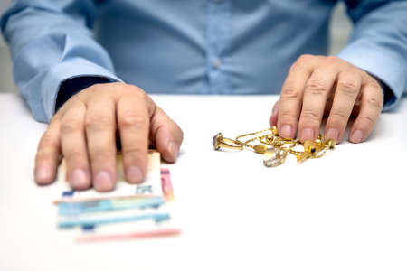 Sell gold jewellry, pawnbroker with euro banknots in hand, sale and buying