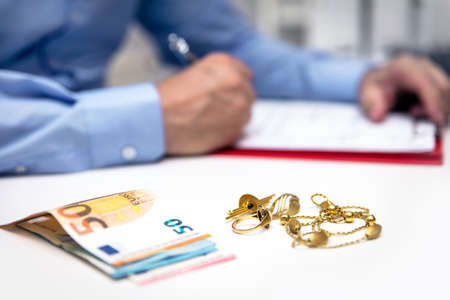 Businessman in the back, euro banknotes and gold jewellry in the front, disposal and selling Stockfoto