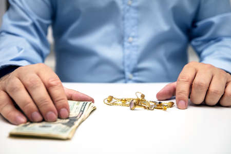 Sell gold jewellry, pawnbroker with us dollars in the hand, sale and buying