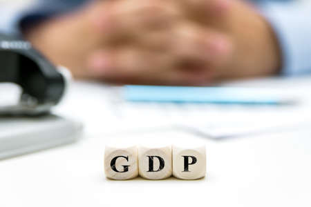 Office with man in the background, dice with word GDP, gross domestic product, english word