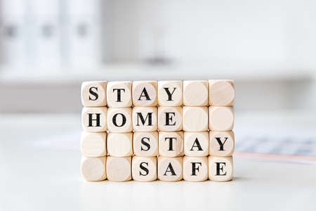 many wooden blocks in a bright office or practice with the words stay home stay safe