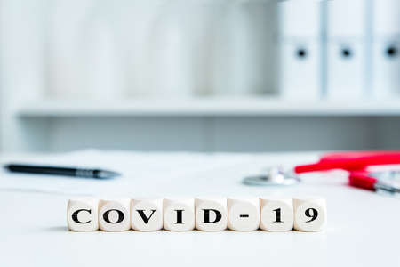 Dices with word covid-19 in a medical workplace, clinic or doctor's office, coronavirus and healthcare