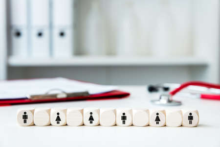 medical practice with wooden blocks and symbols for men and women, concept social distancing or safe distance Stockfoto