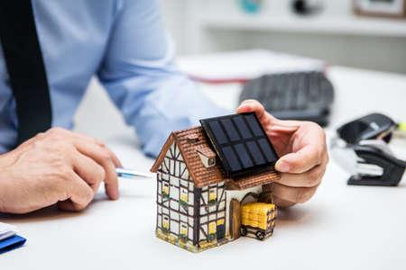 Businessman holding a solar panel on a symbolic farmhouse, green energy and economy Stockfoto