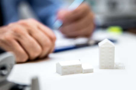 Real estate agent with symbolic houses and building projects, 3-d concept Stockfoto