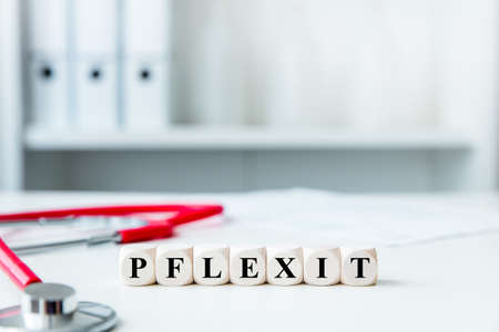 Medical office with dices, german word pflexit witch means pflege and exit, healthcare and new law Stockfoto