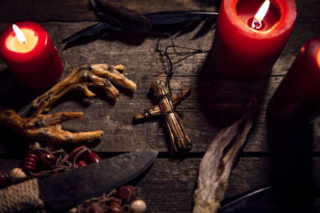 Dark Voodoo or vodun ritual with puppet, crow's feet and knife, african witchcraft and religion