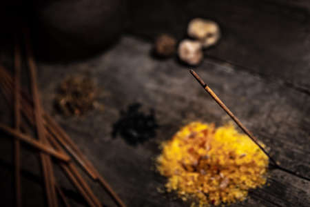 Resin, styrax, dried herbs and incense on wooden table, esoteric and meditation materials