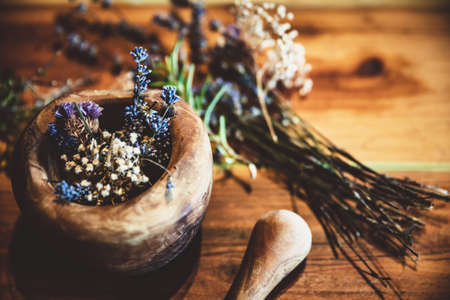 Ritual purification and cleansing with dried healing herbs and flowers, natural background